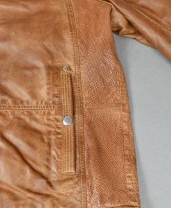 Détail de la poche du Blouson en cuir teinte acajou, empiècements perforés sur les côtés, style moderne et urbain.