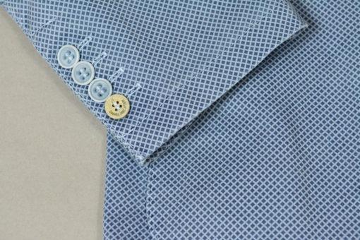 Boutonnage détail, Veste deux boutons bleue motif quadrillage en losange, style urbain.